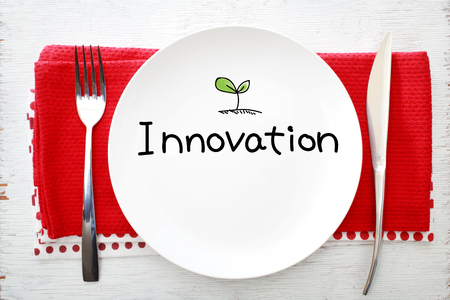 napkins: Innovation concept on white plate with fork and knife on red napkins