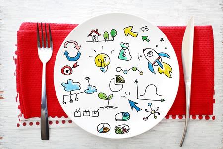 Concepto de la creatividad en un plato blanco con un tenedor y un cuchillo en servilletas rojas Foto de archivo - 46187782