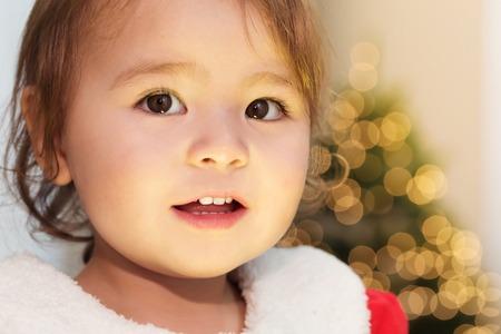 niños sonriendo: Muchacha feliz del niño sonriente delante de su árbol de Navidad