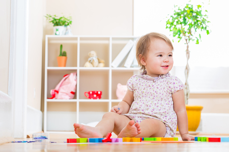 baby toys: Happy toddler girl smiling while playing with toy blocks