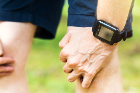 running man: Male runner wearing a smart watch resting outside Stock Photo