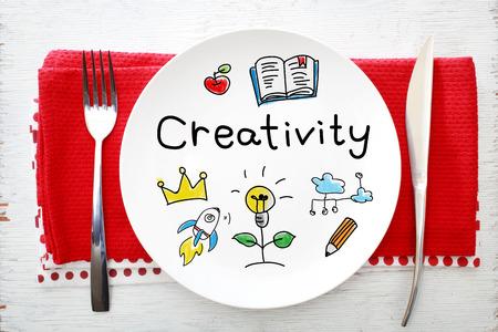 inspiracion: Concepto de la creatividad en un plato blanco con un tenedor y un cuchillo en servilletas rojas