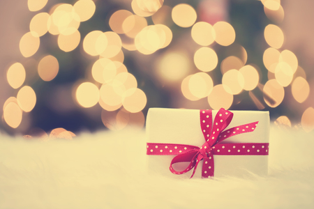 Christmas gift box on white carpet in frot of tree