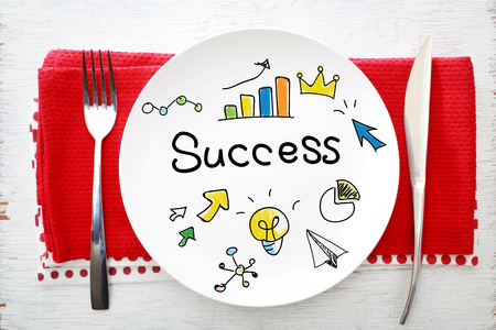 napkins: Success concept on white plate with fork and knife on red napkins Stock Photo