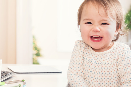 Cheerful toddler girl with a huge smile sitting at a desk in her house Standard-Bild