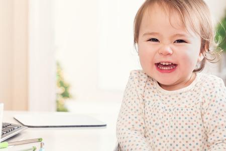 Vrolijke peuter meisje met een grote glimlach zittend aan een bureau in haar huis