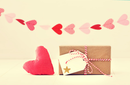 giftwrapped: A garland of hearts above a small gift-wrapped box and red textile heart on a neutral white background with copyspace