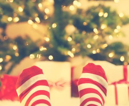 under the tree: Feet with striped socks with Christmas gift boxes under the tree