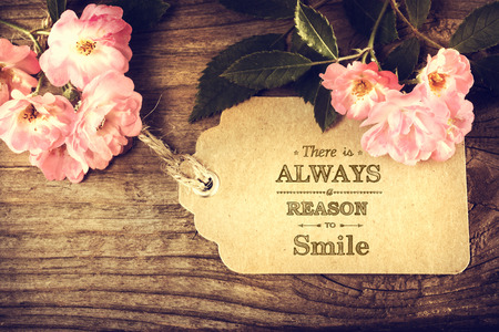 There is always a reason to smile message with small roses on rustic wooden table Stock Photo