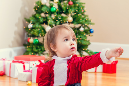 santa suit: Little toddler girl in a santa suit playing under the Christmas tree Stock Photo