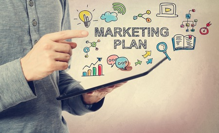 koncept: Ung man pekar på marknadsföringsplan koncept över en tablett dator