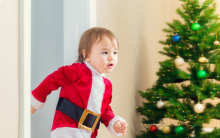 dashing: Little toddler girl in a santa suit dashing to open her Christmas presents