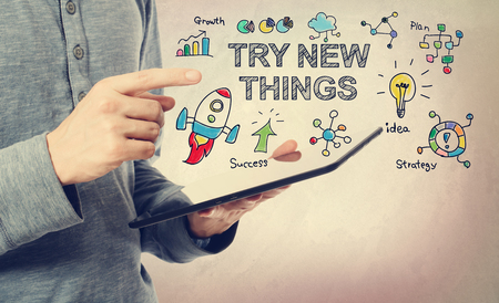 Young man pointing at Try New Things concept over a tablet computer Stock Photo