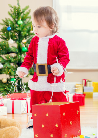 santa suit: Little toddler girl in a santa suit playing by the Christmas tree