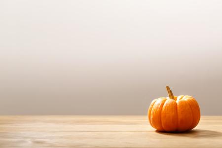 Herfst oranje kleine pompoen op een houten tafel Stockfoto
