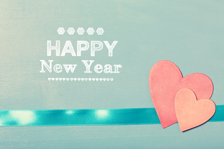 paper board: Happy New Year message with pink paper hearts on blue wooden board Stock Photo
