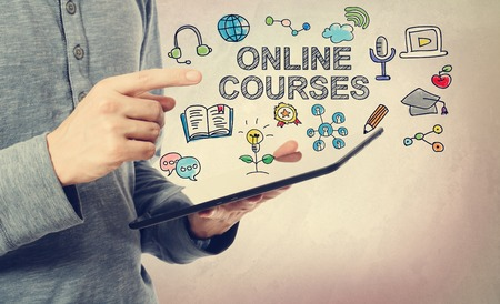 Young man pointing at Online Courses concept over a tablet computer