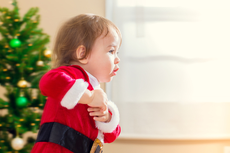 santa suit: Little toddler girl in a santa suit running to open Christmas presents