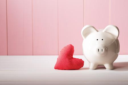 赤いハート ピンクの木製壁に枕で貯金