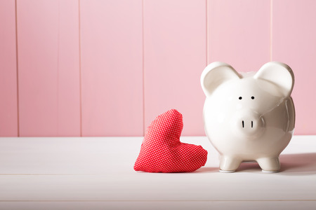 Piggy bank with red heart pillow on pink wooden wall Imagens