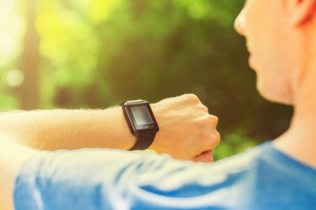 Man looking at his smart watch outside at sunset