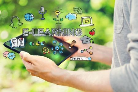 Concepto del aprendizaje electrónico con el hombre joven que sostiene su computadora de la tableta fuera en el parque