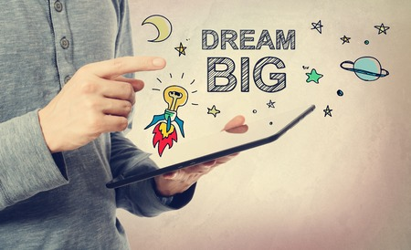 hope: Young man pointing at Dream BIG concept over a tablet computer Stock Photo