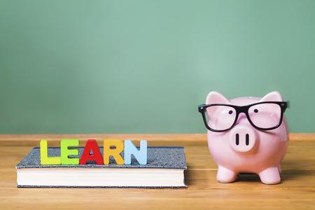 Lernthema mit rosa Sparschwein mit Tafel im Hintergrund als Konzeptbild der Kosten der Bildung Standard-Bild - 46164206