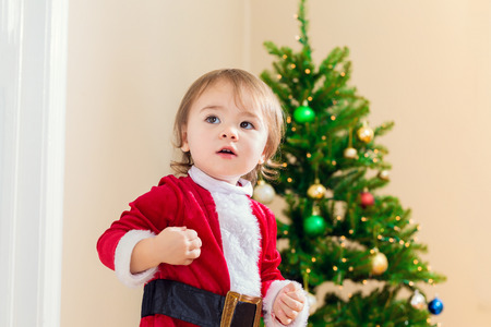 santa suit: Little toddler girl in a santa suit excited for Christmas Stock Photo