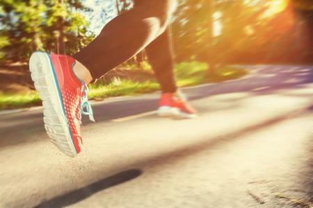 personas trotando: Corredor de la mujer corriendo por una pista al aire libre al atardecer