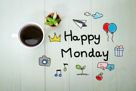 Happy Monday message with a cup of coffee on a pastel wooden table Archivio Fotografico