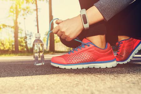 Kobieta jogger wiążąc swoje buty do biegania na zewnątrz