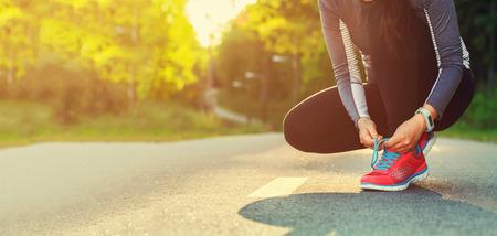 zapato: Corredor femenino atarse los zapatos que se preparan para una carrera a correr fuera