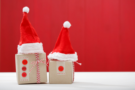 little table: Christmas little gift boxes with Santa hats on red colored wooden board
