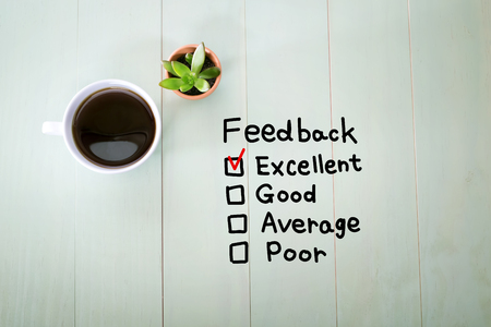 Feedback concept with a cup of coffee on a pastel wooden table