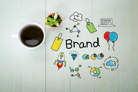brands: Brand concept with a cup of coffee on a pastel wooden table Stock Photo