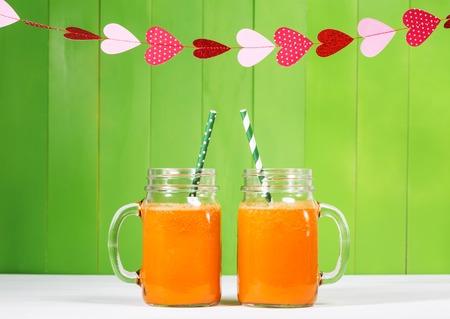 vaso de jugo: El jugo de zanahoria en albañiles frascos en el fondo de madera verde