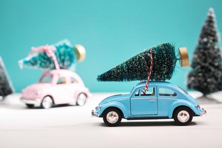 carritos de juguete: Coche lleva un árbol de Navidad en una nieve cubierto bosque siempre verde miniatura