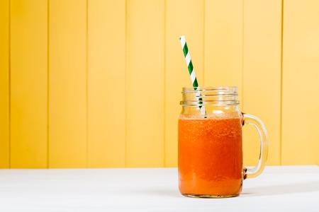 batidos de frutas: El jugo de zanahoria en albañiles tarro en fondo amarillo de madera Foto de archivo