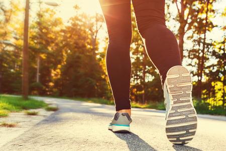 hacer footing: Mujer en zapatos para correr dispuestos a correr fuera de la puesta del sol
