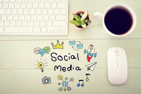 concept de médias sociaux avec la station de travail sur un bureau en bois clair