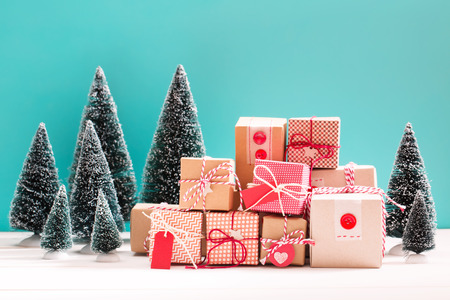 little table: Collection of little handmade gift boxes in a snow covered miniature evergreen forest Stock Photo