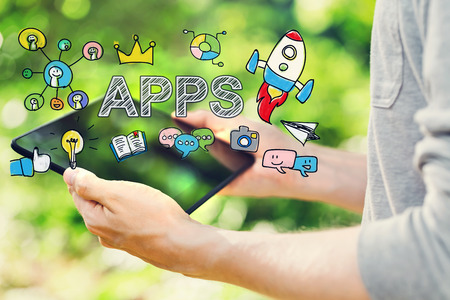 mobile app: APPS concept with young man holding his tablet computer outside in the park Stock Photo
