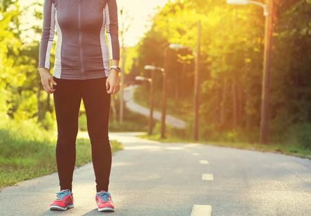 hacer footing: atleta femenina que se prepara para correr en una pista forestal en la puesta del sol