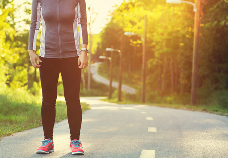 jog: Female athlete preparing for a jog on a forest path at sunset Stock Photo