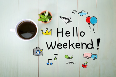 encouragements: Hello Weekend message with a cup of coffee on a pastel wooden table