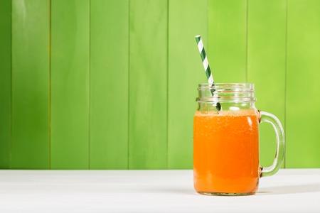 verre de jus d orange: Le jus de carotte dans maçons pot sur fond de bois vert