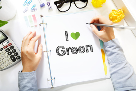business environment: Person drawing I Love Green concept on white paper in the office Stock Photo