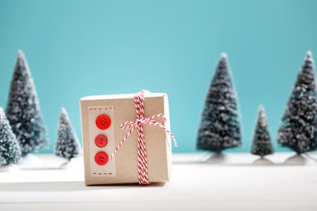 decoracion mesas: caja de regalo hecho a mano en un bosque cubierto de nieve �rbol de hoja perenne en miniatura