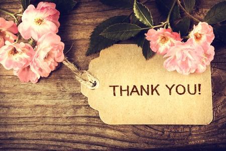 agradecimiento: Gracias mensaje con peque�as rosas en el fondo de madera